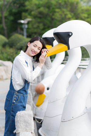 chinese adult: happy girl enjoying her time with the duck like boat