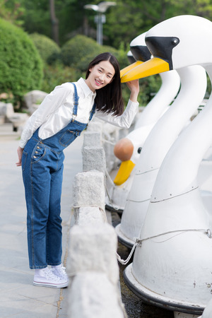 chinese adult: girl smiled happily and taking photos with the duck like boats