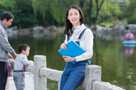 chinese adult: reading girl standing beside the lakeside, asian woman Stock Photo