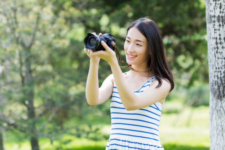 asian adult: girl taking photos in the park