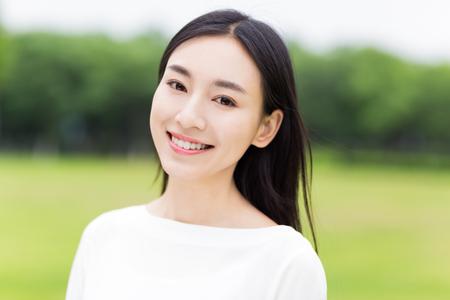 lächeln: Mädchen mit weißen Kleid im Park