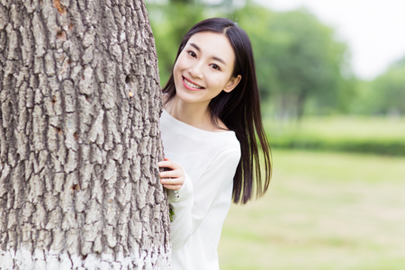 hide and seek: a vivacious girl hiding behind of the tree, playing hide and seek