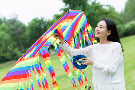 asian lifestyle: cute chinese girl flying a kite in the park Stock Photo