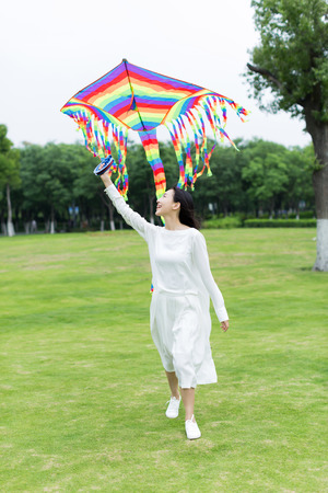 flying woman: young  woman flying a colorful kite in the park