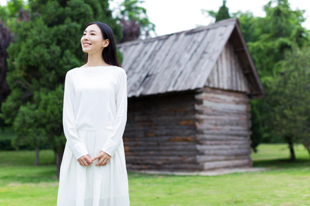 long hair woman: young  chinese woman, standing alone in front of the Cabin village, taking a breath of fresh air