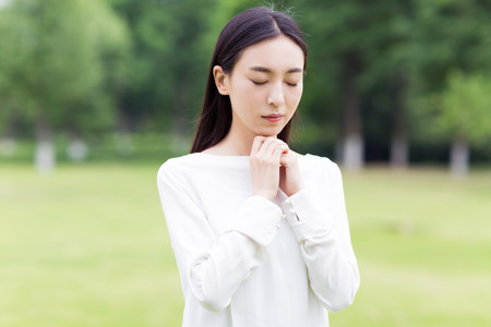 silently: chinese girl praying silently in the park Stock Photo
