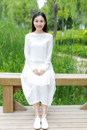asian adult: girl with white dress sitting on the bench Stock Photo