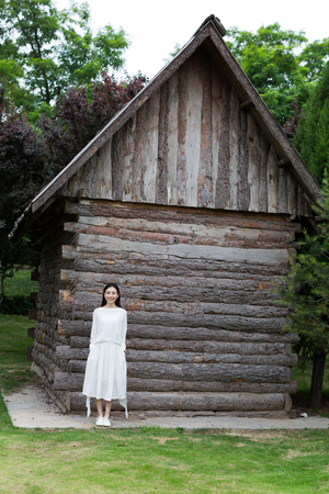 breath taking: young chinese woman, standing alone in front of the Cabin village, taking a breath of fresh air Stock Photo