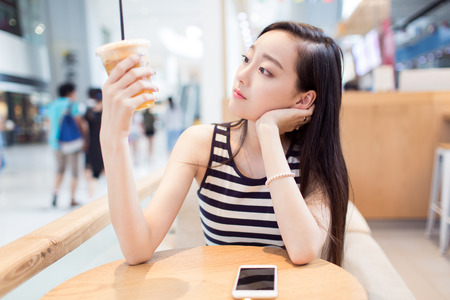 mobile phones: chinese girl, sitting alone in a coffee shop Stock Photo