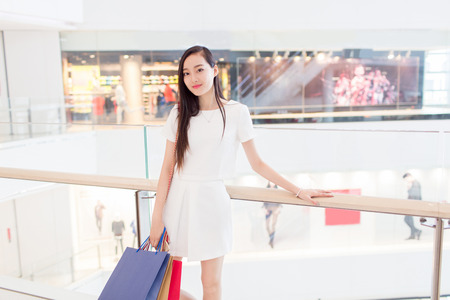 trading floor: chinese young girl with stylish white dress enjoying her shopping time