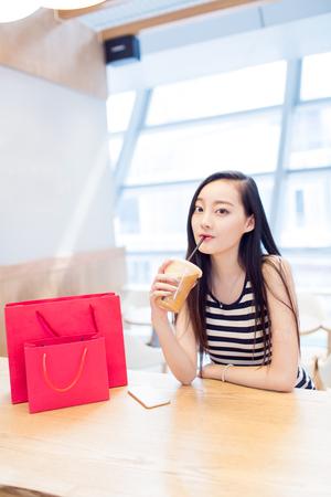 쇼핑몰에서 커피 한잔을 가지고 중국 어린 소녀