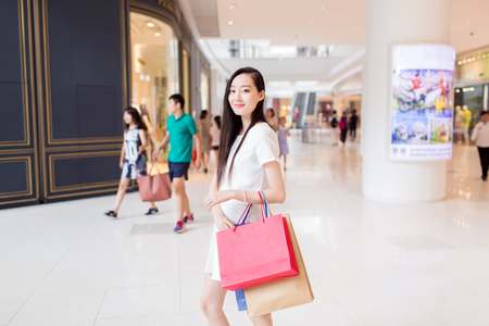 lifestyle shopping: chinese young girl, wearing a stylish white dress, walking in the mall