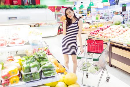 asian girl shopping: chinese girl enjoying her grocery shopping in supermarket Stock Photo