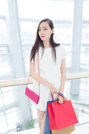 casual fashion: young chinese girl with her shopping bags