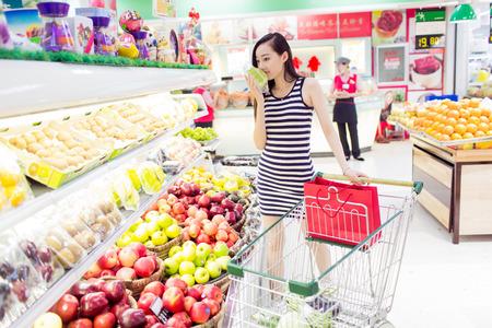 슈퍼마켓에서 쇼핑하는 그녀의 식료품 점을 즐기는 중국 소녀