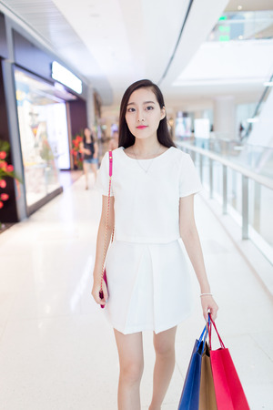young black girl: young chinese girl with her shopping bags