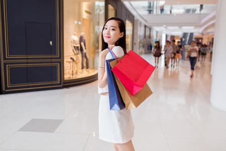 그녀의 쇼핑 가방과 함께 젊은 중국 여자 스톡 콘텐츠