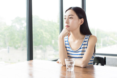 chinese girl sitting beside of the windows and waiting for someone Stock Photo
