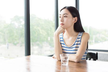 tomando agua: muchacha china se sienta al lado de las ventanas y esperar a que alguien Foto de archivo