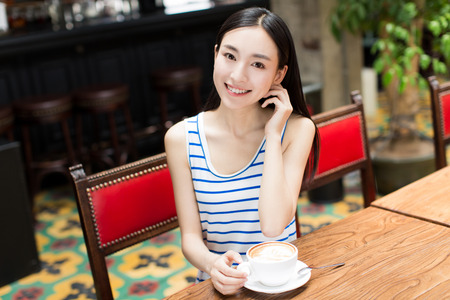 카페에서 그녀의 음료를 즐기는 중국 여자 스톡 콘텐츠