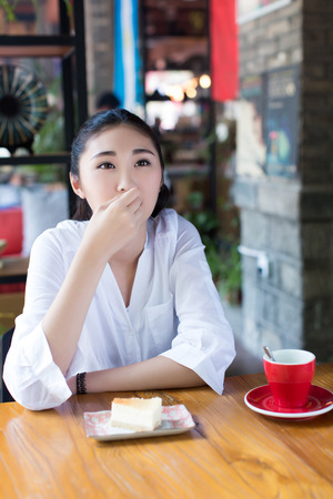 long weekend: beautiful chinese students eating her favorite cake dessert in