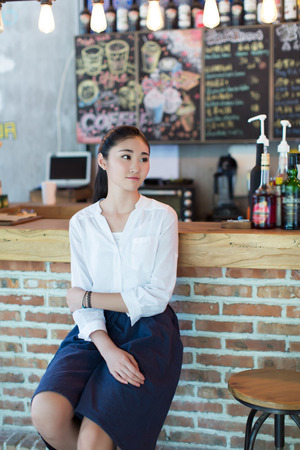 sitting pretty: pretty girl sitting on retro-style bar and look outside