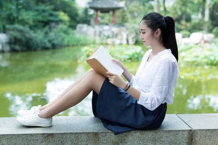 niñas chinas: en el hermoso lago, una muchacha china que mira su revista Foto de archivo