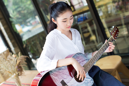 faldas: beautiful chinese black hair girl playing acoustic guitar over indoor