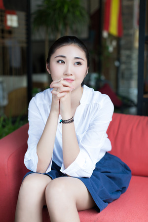 red sofa: pretty chinese girl, sitting on a red sofa smiling