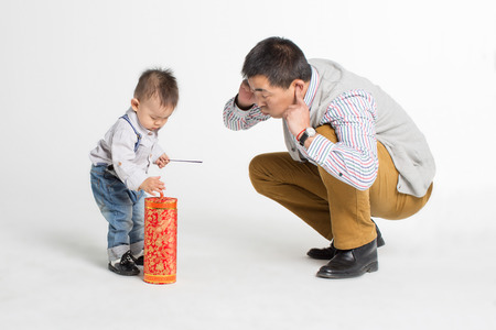 Portrait of a father and son playing fire cracker Standard-Bild
