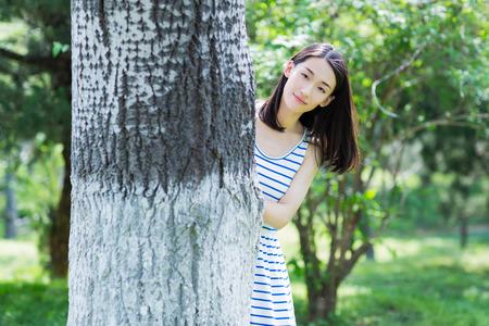 hide and seek: chinese girl playing hide and seek in park