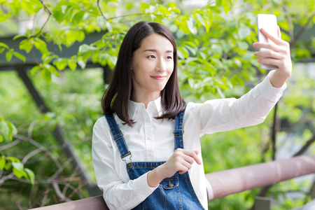 asian natural: chinese girl taking self portrait in the park
