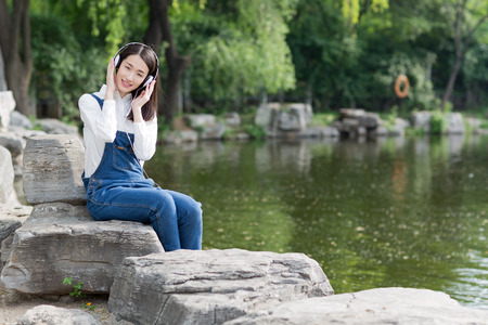 chinese adult: chinese girl sitting beside of the lake and enjoying her music