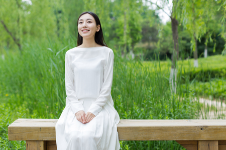 green grass: girl in the park in a white dress on a sunny day Stock Photo