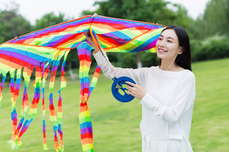 laughing girl: Chinese girl flying a kite in the park