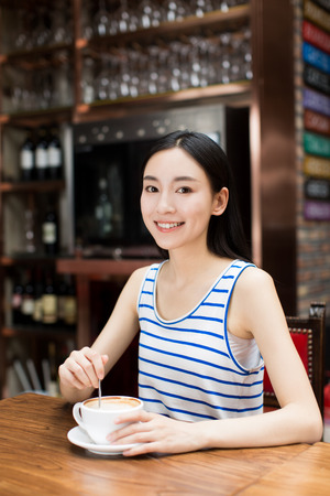 stirring: Young lady drinking a cup of coffee in a cafe Stock Photo