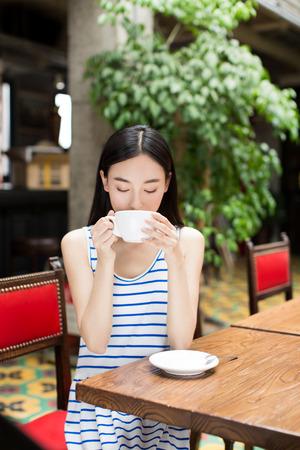 tarde de cafe: mujer que bebe una taza de café y sonriente