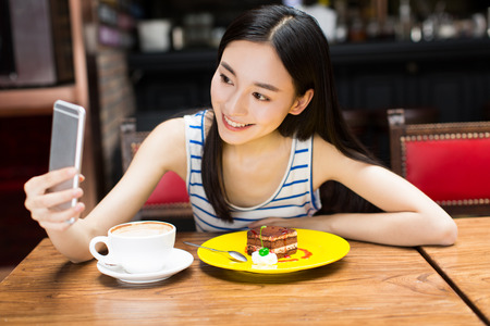 asian ethnicity: smiling young chinese woman taking a selfie in a cafe