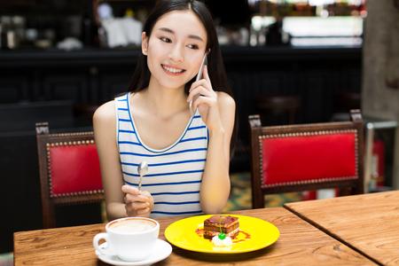 tarde de cafe: joven disfrutando de pastel de chocolate en un restaurante