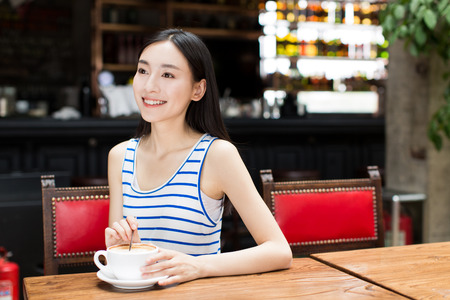 long weekend: portrait of attractive asian girl enjoying cup of hot coffee in the morning.