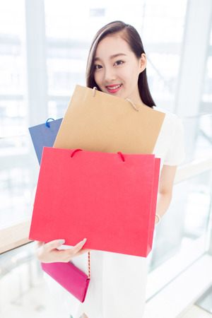 lifestyle shopping: young chinese girl holding bags
