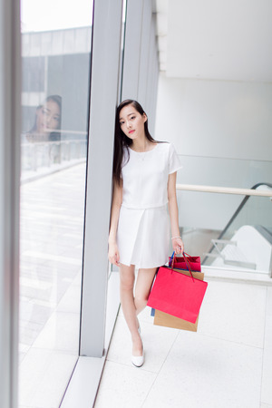 trading floor: chinese long-haired girl carrying shopping bags standing