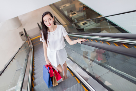 trading floor: stylish chinese girl holding shopping bags at the mall