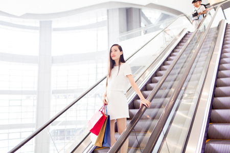 trading floor: stylish girl holding shopping bags at the mall