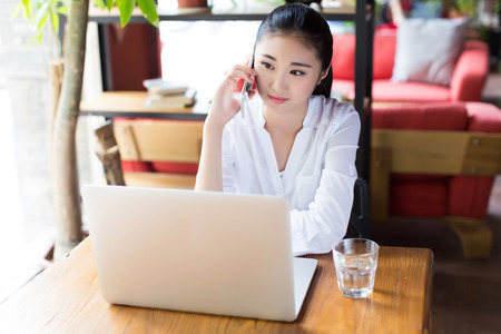 girl with laptop: portrait of a woman talking on the phone while sitting in the cafe and enjoying coffee