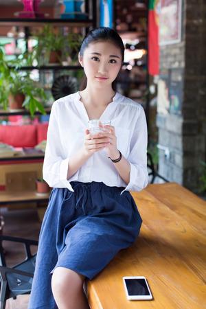 niñas chinas: mujer joven de pelo negro hablando por el móvil sentado en una mesa en un café Foto de archivo