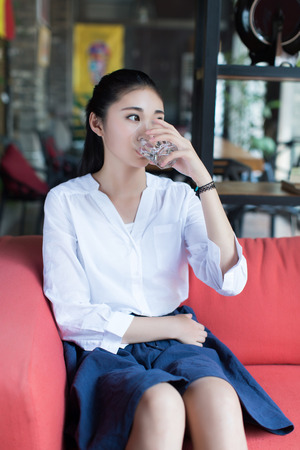 tomando agua: Una ni�a sentada en un sof� rojo y beber un vaso de agua
