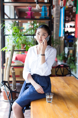 young black hair woman talking on the cellphone sitting on a table in a cafe photo