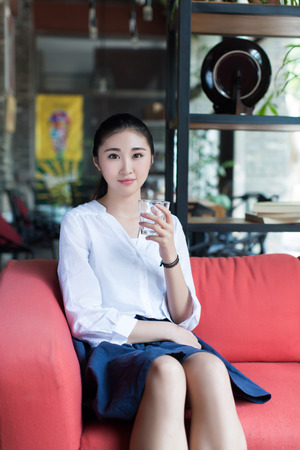 Young girl sitting on a red sofa in a cafe photo