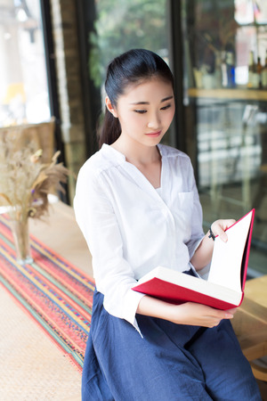 portrait of a young woman sitting at the park cafe table and reading book photo